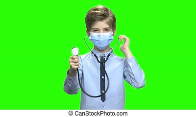 Cute boy with medical mask using stethoscope. Green hromakey...