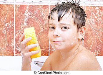Cute boy with sponge in bathtub