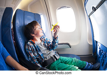 Cute boy with toy plane sit by the airplane window