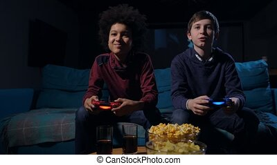 Cute boys competing in video game on home console - Diverse...