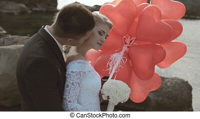 Cute bride and groom stand with balloons in the form of heart in the rocks by the sea