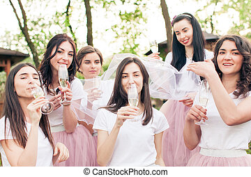 Cute bride and happy bridesmaids drinking champagne at hen-party