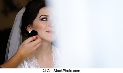 Cute bridesmaid in blue dress applying make-up for a young beautiful bride wearing white silk rest gown and a veil .