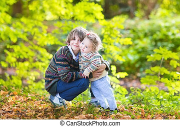 Cute brother and his baby sister hugging and playing together in