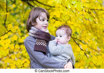 Cute brother and his baby sister playing in a park with yellow a