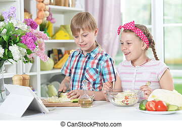 Cute brother and sister cooking together at home