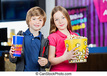 Cute Brother And Sister Holding Snacks At Cinema