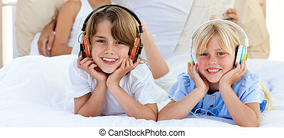 Cute brother and sister listening music with headphones lying on bed