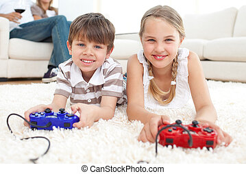 Cute brother and sister playing video games