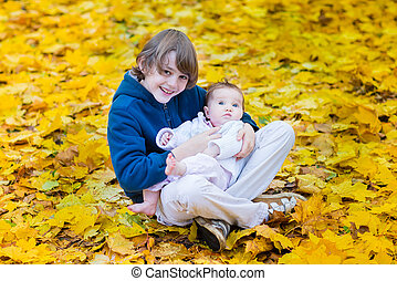 Cute brother holding his baby sister playing between yellow mapl