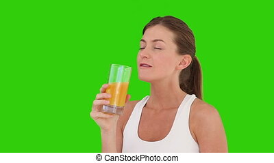Cute brown-haired woman drinking orange juice
