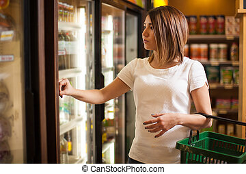 Cute brunette buying some groceries
