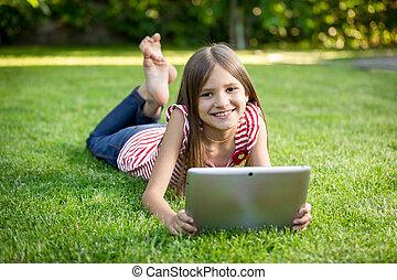 brunette girl relaxing on grass park and holding digital tablet