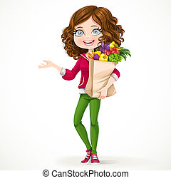 Cute brunette girl with curly hair holding a paper bag with fruit and vegetables standing on a white background