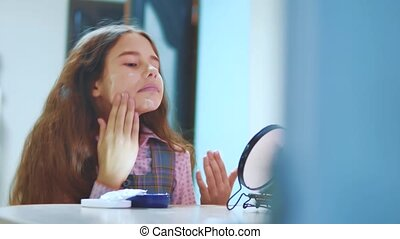 Cute brunette Hispanic little girl putting cream on her...