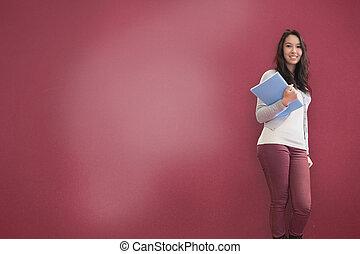 Cute brunette holding notebook posing