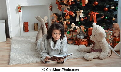 cute brunette lies near the Christmas tree and reading a book