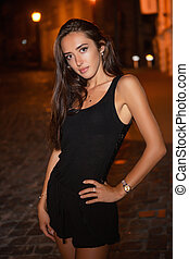 Cute brunette posing at night outdoors.