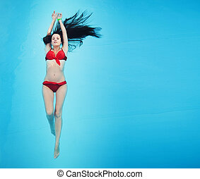 Cute brunette relaxing in a swimming pool