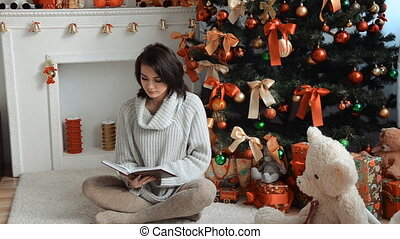 cute brunette sitting near a Christmas tree and looks into the book