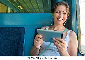 cute brunette with a tablet sitting in the subway