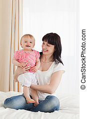 Cute brunette woman holding her baby on her knees while sitting on a bed in her appartment
