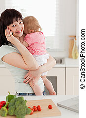 Cute brunette woman on the phone while holding her baby in her arms in the kitchen