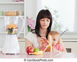 Cute brunette woman pealing a banana while holding her baby on her knees in the kitchen