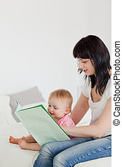 Cute brunette woman showing a book to her baby while sitting on a bed in her appartment