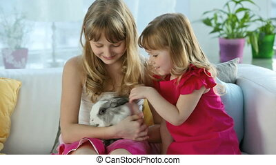 Sisters sitting on the sofa lovingly and gently stroking a cute bunny, Easter series