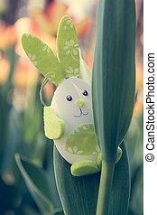 Cute bunny toy hidding among tulips.