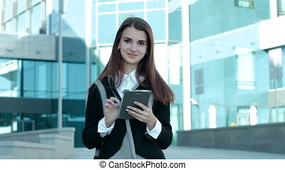 business girl works with a mobile tablet and smiles into the camera on the street