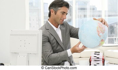 Cute businessman holding a globe