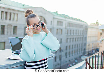 Cute businesswoman in eyeglasses talking on the phone standing on the roof of the house in the old town. Next to it are a laptop, smartphone and paper documents.
