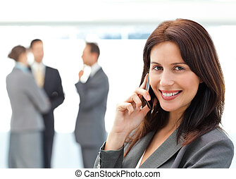 Cute businesswoman on the phone while her team discussing