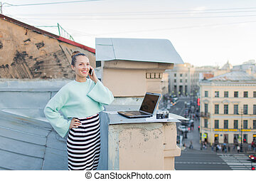 Cute businesswoman talking on the phone standing on the roof of the house in the old town. Next to it are a laptop, smartphone and paper documents