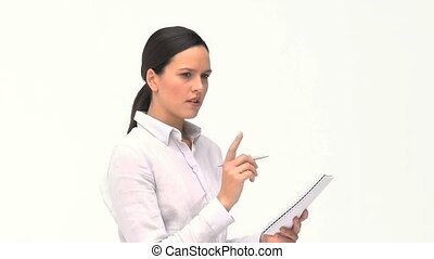 Cute businesswoman writing on her notebook against a white...