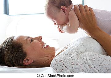 cute, cama, segurando, mãe, bebê, feliz