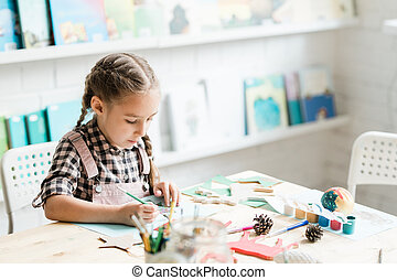 Cute casual schoolgirl with paintbrush drawing Christmas picture by desk