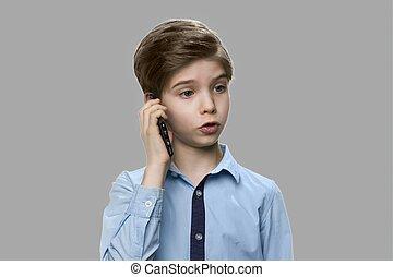 Cute caucasian boy talking on cell phone.