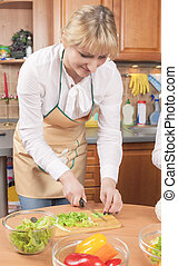 Cute Caucasian Female Preparing Vegetables For Salad in The Kitchen. Vertical Image