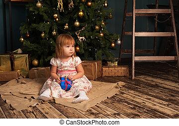 Cute caucasian girl sitting near Christmas tree