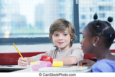 Cute caucasian kid at classroom desk drawing and smiling to his