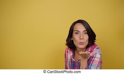 Cute charming lady send air kiss in plaid shirt on a yellow background looking at camera. Facial expressions, emotions, feelings. High quality 4k footage.