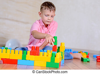 Cute cheeky young boy playing at home with colorful plastic building blocks holding up a toy to the camera with a grin