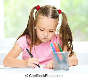 Cute cheerful child drawing using felt-tip pen while sitting...