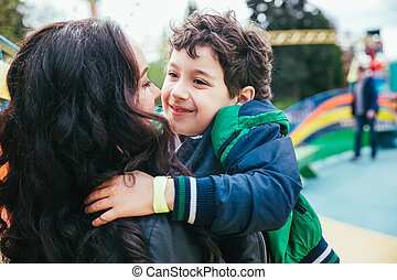 Cute cheerful child with mother play outdoors in park.