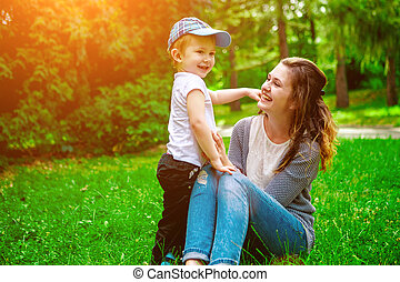 Cute cheerful child with mother play outdoors