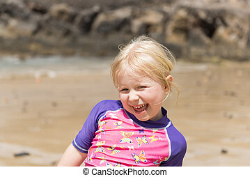 Cute Cheerful Little Girl with Beach in the Background