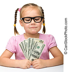Cute cheerful little girl with paper money - dollars,...